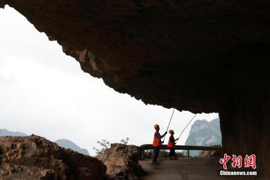 6月21日,黄启富(左)和杨志辉在清理公路顶部的落石隐患。贵州省毕节市赫章县白果街道石板河村是一个深度贫困村,过去只能靠一条悬崖上的羊肠小道通往村外。2000年至2003年间,石板河村村民从村旁的川沟大岩上开凿一条长700多米的挂壁公路通往村外,这条通村路于2016年经过硬化变成了一条约4.5米宽水泥公路。今年50岁的黄启富是石板河村的一名建档立卡贫困户,当年全程参与了挂壁公路的建设。2003年公路建成后,黄启富就开始了义务管护这段挂壁公路,十多年如一日从不间断。2017年,当地政府设立就业扶贫公益专岗,聘请贫困户为护路员,黄启富和同村的贫困户杨明顺、杨志辉成了因此石板河村挂壁公路的护路员。中新社发 韩贤普 摄 图片来源:CNSPHOTO