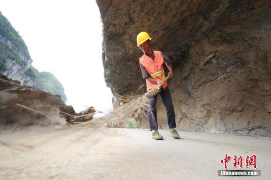 6月21日,黄启富在清扫石板河村挂壁公路。中新社发 韩贤普 摄 图片来源:CNSPHOTO