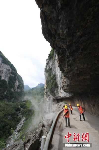 6月21日,黄启富和杨明顺、杨志辉在前往清扫石板河村挂壁公路。中新社发 韩贤普 摄 图片来源:CNSPHOTO
