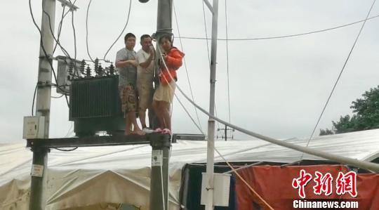 民众被困电杆,消防员施救。廖二攀 摄