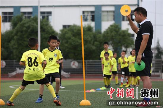 6月22日,在贵州省丹寨县城关第一小学,足球小球员们在教练的指导下做步伐移动训练。 黄晓海 摄
