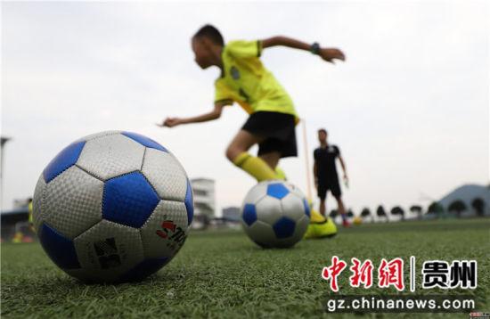 6月22日,在贵州省丹寨县城关第一小学,足球小球员们在做带球训练。黄晓海 摄