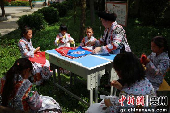 6月26日,在贵州省毕节市黔西县林泉镇高锦小学里,师生们在练习刺绣。