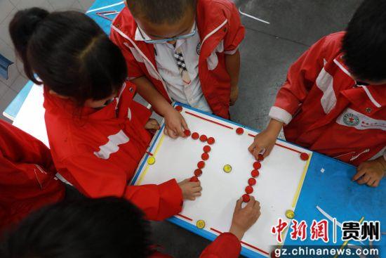 """6月28日,贵州省毕节市黔西县第一小学的小朋友们在用瓶盖摆出""""七一""""图案。"""