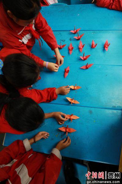 """6月28日,贵州省毕节市黔西县第一小学的小朋友们在折叠纸飞机摆""""七一""""图案。"""