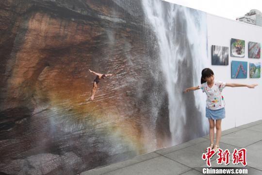 图为一位小朋友在模仿照片里跳水运动员的动作拍照留念。贺俊怡 摄