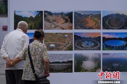 图为两位老人在观看FAST从选址到建成启用的影像。贺俊怡 摄