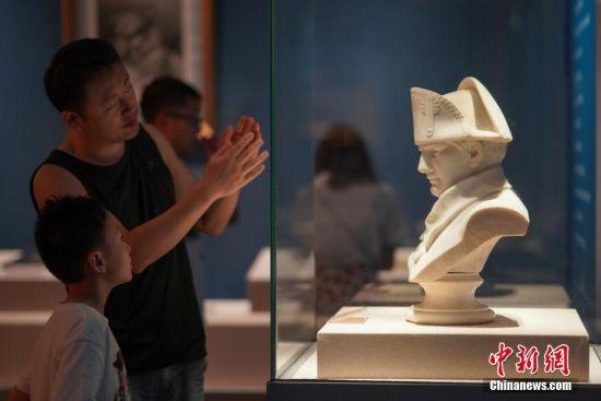 """7月3日,一位父亲在贵州省博物馆给孩子介绍展出的拿破仑一世半身雕塑。""""法兰西的雄鹰――拿破仑文物(中国)巡回展览""""从6月25日至9月1日在贵州省博物馆展出,本次展览共展出展品150余件(套),既包括名家创作的油画、雕塑、版画等艺术品,还包括拿破仑使用过的物品及拿破仑时期的服装、生活用品等,从""""军事思想的形成""""""""帝国理想的实践""""""""欧洲梦想的破灭""""""""时代英雄的落幕""""四个方面展现了拿破仑跌宕起伏的戏剧人生,同时也再现了欧洲艺术文明的辉煌一页。中新社记者 贺俊怡 摄"""