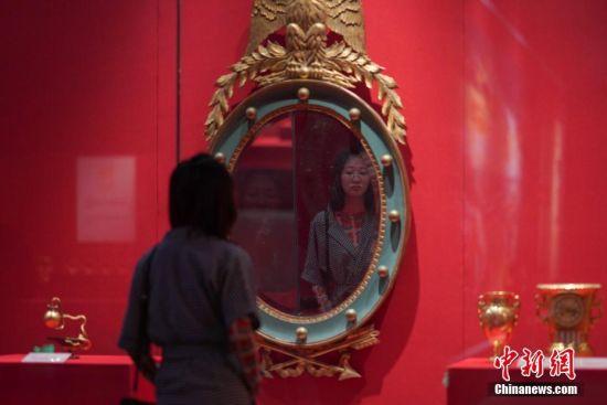 """7月3日,参观者在贵州省博物馆观看展出的宫廷挂镜子。""""法兰西的雄鹰――拿破仑文物(中国)巡回展览""""从6月25日至9月1日在贵州省博物馆展出,本次展览共展出展品150余件(套),既包括名家创作的油画、雕塑、版画等艺术品,还包括拿破仑使用过的物品及拿破仑时期的服装、生活用品等,从""""军事思想的形成""""""""帝国理想的实践""""""""欧洲梦想的破灭""""""""时代英雄的落幕""""四个方面展现了拿破仑跌宕起伏的戏剧人生,同时也再现了欧洲艺术文明的辉煌一页。中新社记者 贺俊怡 摄"""