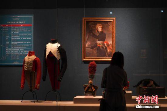 """7月3日,参观者在贵州省博物馆观看展出的禁卫军服饰。""""法兰西的雄鹰――拿破仑文物(中国)巡回展览""""从6月25日至9月1日在贵州省博物馆展出,本次展览共展出展品150余件(套),既包括名家创作的油画、雕塑、版画等艺术品,还包括拿破仑使用过的物品及拿破仑时期的服装、生活用品等,从""""军事思想的形成""""""""帝国理想的实践""""""""欧洲梦想的破灭""""""""时代英雄的落幕""""四个方面展现了拿破仑跌宕起伏的戏剧人生,同时也再现了欧洲艺术文明的辉煌一页。中新社记者 贺俊怡 摄"""
