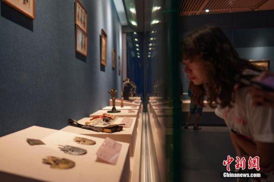 """7月3日,参观者在贵州省博物馆观看展出的骑兵挎包、军队弹夹带模型、军队帽子饰品等物件。""""法兰西的雄鹰――拿破仑文物(中国)巡回展览""""从6月25日至9月1日在贵州省博物馆展出,本次展览共展出展品150余件(套),既包括名家创作的油画、雕塑、版画等艺术品,还包括拿破仑使用过的物品及拿破仑时期的服装、生活用品等,从""""军事思想的形成""""""""帝国理想的实践""""""""欧洲梦想的破灭""""""""时代英雄的落幕""""四个方面展现了拿破仑跌宕起伏的戏剧人生,同时也再现了欧洲艺术文明的辉煌一页。中新社记者 贺俊怡 摄"""