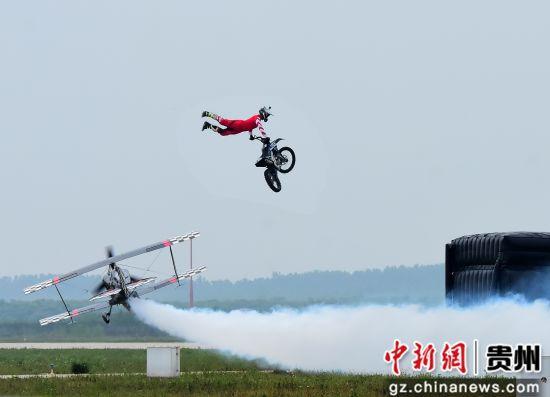 摩托车手驾驶摩托车飞跃正在低飞的Pitts飞机。第一通航供图