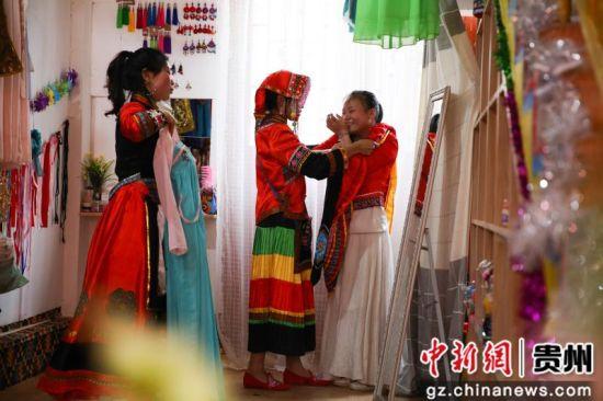 7月4日,在贵州省毕节市大方县奢香古镇聚民艺彝族文化服饰店,龙恩碧正在帮顾客挑选服装。