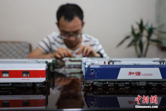 """7月4日,张宇琦拼装火车模型。今年27岁的张宇琦是贵阳北动车运用所的一名动车机械师,同时他也是一个""""火车迷"""",从2012年开始收藏、制作各类火车模型,七年多来他已经收藏了内燃机车、电力机车等火车模型百余节。中新社记者 瞿宏伦 摄"""