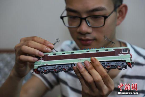 """7月4日,张宇琦调节火车模型的""""受电弓""""。今年27岁的张宇琦是贵阳北动车运用所的一名动车机械师,同时他也是一个""""火车迷"""",从2012年开始收藏、制作各类火车模型,七年多来他已经收藏了内燃机车、电力机车等火车模型百余节。中新社记者 瞿宏伦 摄"""