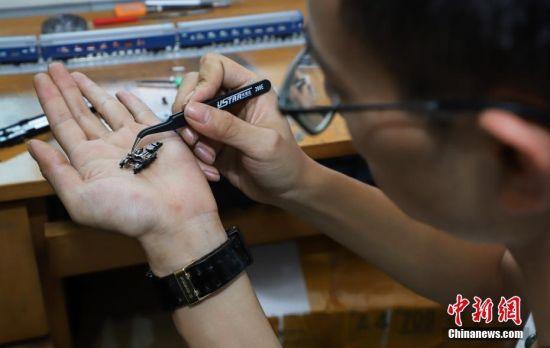 """7月4日,张宇琦维修火车模型零部件。今年27岁的张宇琦是贵阳北动车运用所的一名动车机械师,同时他也是一个""""火车迷"""",从2012年开始收藏、制作各类火车模型,七年多来他已经收藏了内燃机车、电力机车等火车模型百余节。中新社记者 瞿宏伦 摄"""