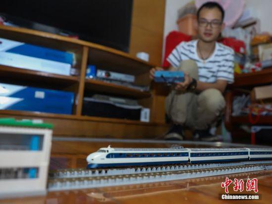 """7月4日,张宇琦用控制器控制动车模型行驶。今年27岁的张宇琦是贵阳北动车运用所的一名动车机械师,同时他也是一个""""火车迷"""",从2012年开始收藏、制作各类火车模型,七年多来他已经收藏了内燃机车、电力机车等火车模型百余节。中新社记者 瞿宏伦 摄"""