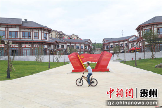 黔西县锦绣街道锦绣社区的孩子骑着自行车在广场上快乐地奔跑。陈龙 摄