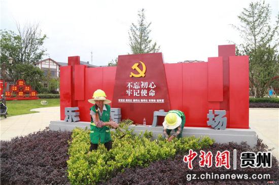 黔西县锦绣街道锦绣社区乐居广场前,搬迁入住的群众在管护绿化树