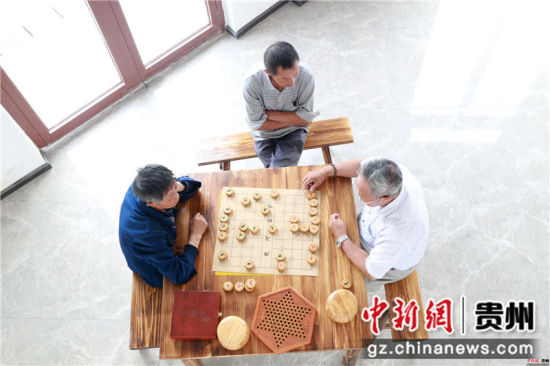 黔西县锦绣街道综合文化服务站内,群众在开心地下象棋。陈龙 摄