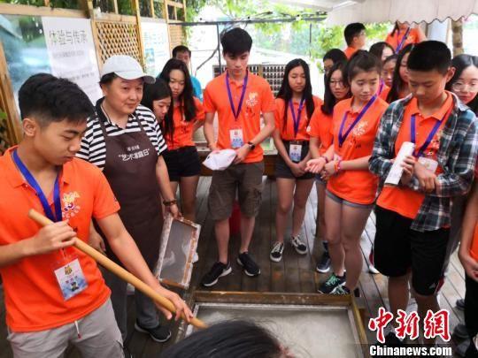 在老师的指导下,海外青少年体验古法造纸。 陈静 摄
