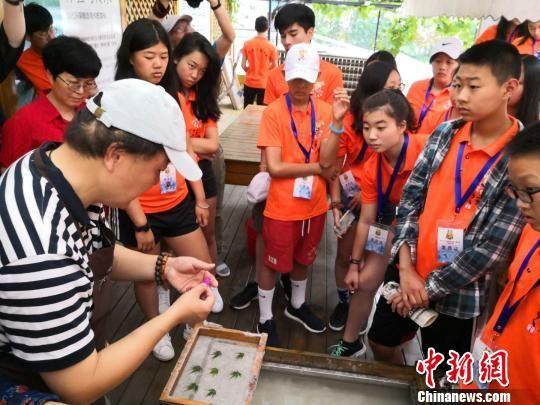 老师指导青少年们将花瓣和叶子融入造纸过程。 陈静 摄