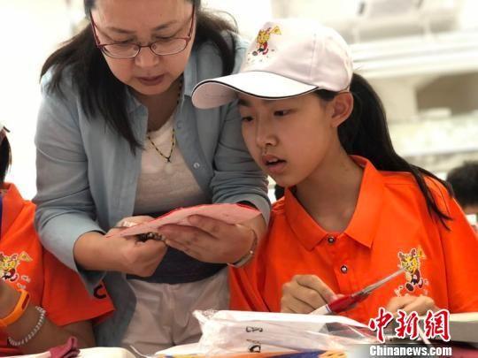 华裔青少年体验剪纸。 窦鹏 摄
