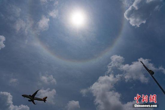 7月10日上午,一架飞机从出现日晕的空中飞过。当日,贵阳市上空出现日晕景观。据了解,日晕也叫圆虹,一种大气光学现象,是日光通过卷层云时,受到冰晶的折射或反射而形成的。中新社记者 贺俊怡 摄