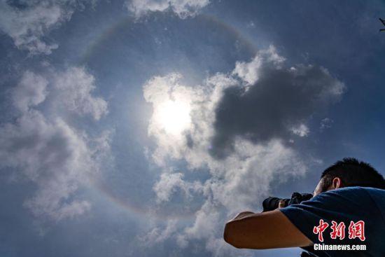7月10日上午,一名摄影爱好者拍摄天空出现的日晕。当日,贵阳市上空出现日晕景观。据了解,日晕也叫圆虹,一种大气光学现象,是日光通过卷层云时,受到冰晶的折射或反射而形成的。中新社记者 贺俊怡 摄