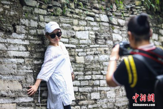 7月13日,一名游客在贵阳青岩古镇景区拍照。青岩古镇是贵州四大古镇之一,建于明洪武十年(1378年),古镇内明清古建筑交错密布,2017年2月古镇被评为中国国家5A级旅游景区。中新社记者 瞿宏伦 摄
