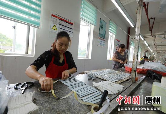 图为工人正在车间制鞋。 胡攀学 摄