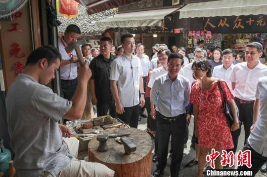越南共产党代表团一行在贵阳市青岩古镇观看苗族银饰锻造。 贺俊怡 摄