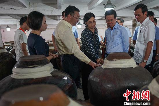7月22日,茅台集团董事长李保芳(前排右四)在酒窖里向武文赏(前排右二)介绍茅台酒。 中新社记者 贺俊怡 摄