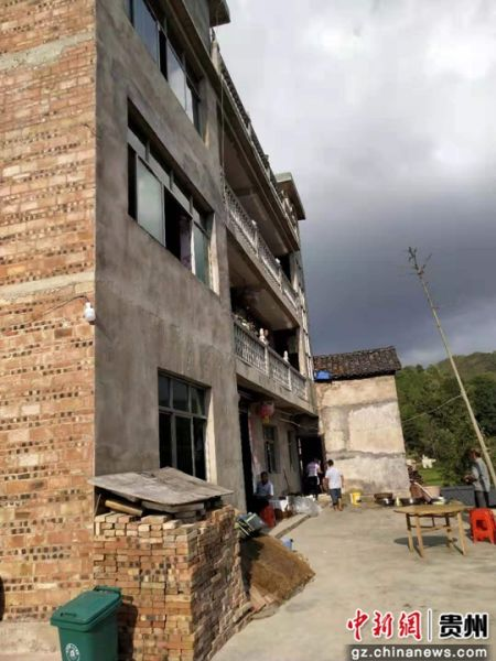 龙成家的三层砖房。
