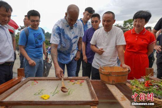 8月2日,马布里(左三)在贵州丹寨体验非遗古法造纸技艺。