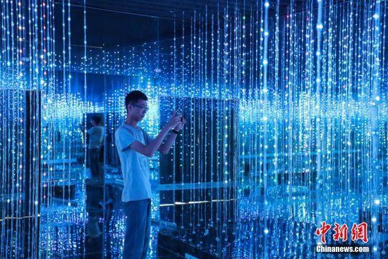 """游客在拍摄""""流光溢彩""""项目。中新社记者 瞿宏伦 摄"""