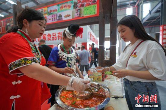 一名观众在辣博会上品尝贵州黔东南苗家酸汤。中新社记者 贺俊怡 摄