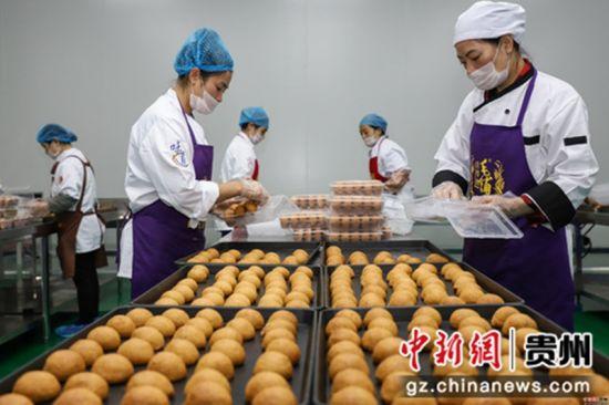 """9月5日,工作人员正在将月饼装盒。中秋佳节来临之际,贵州省贵阳市观山湖区一家月饼生产企业正在加紧赶制月饼,以供应市场所需。该企业生产的月饼是纯手工制作,因口感好而销售火爆,被当地民众称为""""网红月饼""""。"""