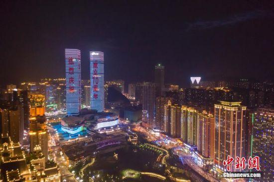 9月24日,贵阳市花果园双子塔上演庆祝中华人民共和国成立70周年灯光秀,吸引市民驻足拍照留念。图为航拍贵阳市花果园双子塔灯光秀。中新社记者 贺俊怡 摄