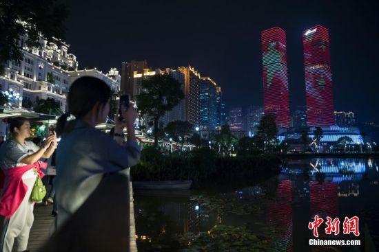 9月24日,贵阳市花果园双子塔上演庆祝中华人民共和国成立70周年灯光秀,吸引市民驻足拍照留念。中新社记者 贺俊怡 摄
