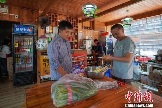 李永福(左)在农家乐里分拣蔬菜。 贺俊怡 摄