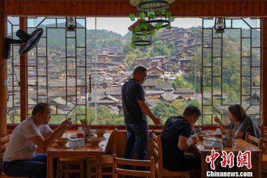 游客在李永福的农家乐里用餐,观景。 贺俊怡 摄