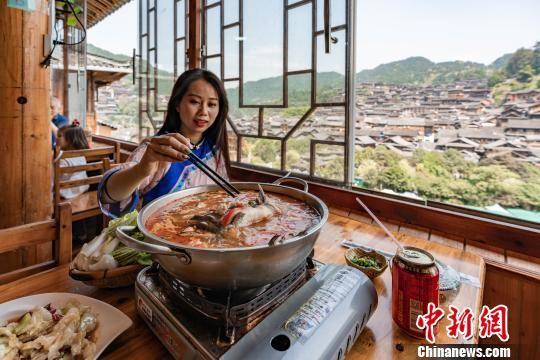 一名游客在李永福的农家乐里吃酸汤鱼。 贺俊怡 摄