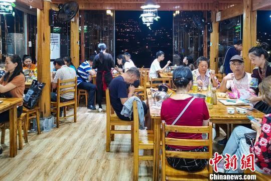 游客在李永福的农家乐用晚餐,窗外是西江苗寨的夜景。 李永福 摄