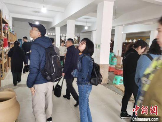11月22日,两岸媒体文化交流参访团来到花茂村。图为参访团成员参观陶器工艺品。 张舵 摄